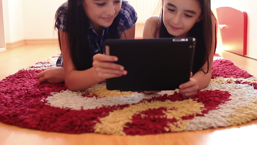 Two happy teenage girls having fun using tablet computer