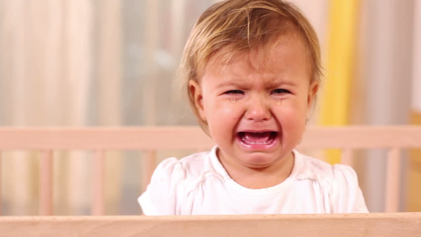 Small girl crying and standing in her bed