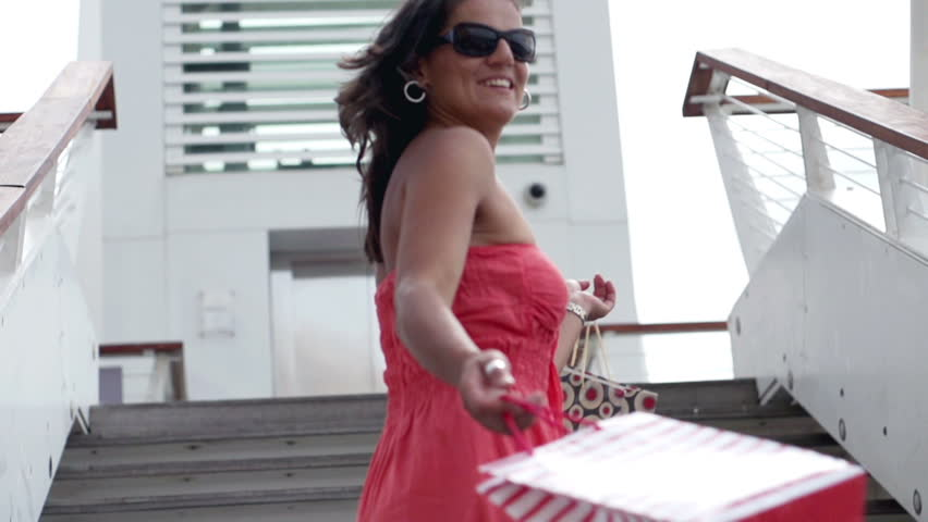 Happy woman after shopping descending the stairs, slow motion shot at 240fps
