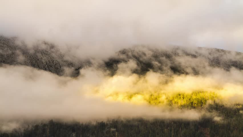 Misty Cloudy Morning with Sun Light Shining on Mountain in BC, Canada. Photo Sequence shot in RAW and Post-Production in After Effects.