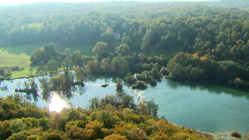 Helicopter flying over a scenic river surrounded by beautiful nature. Aerial shot.