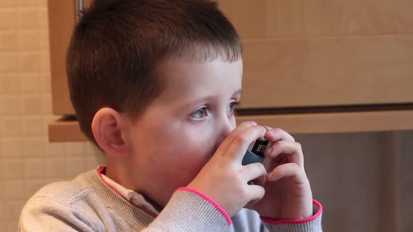 little boy inhaling his asthma pump