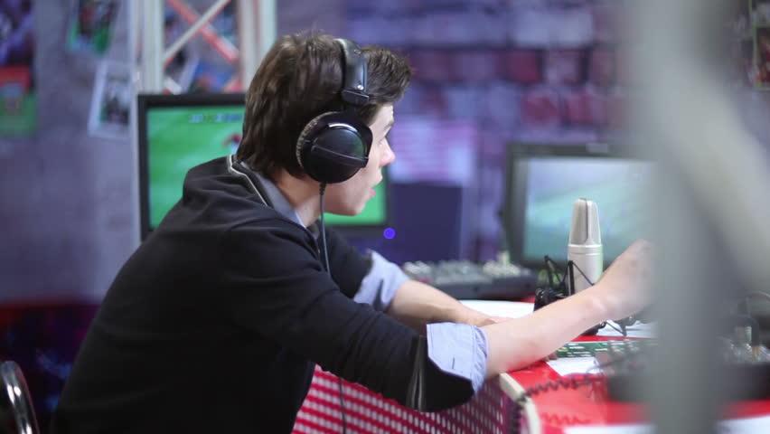 Talking sport event commentator or radio dj in headphones on the air. TV studio
