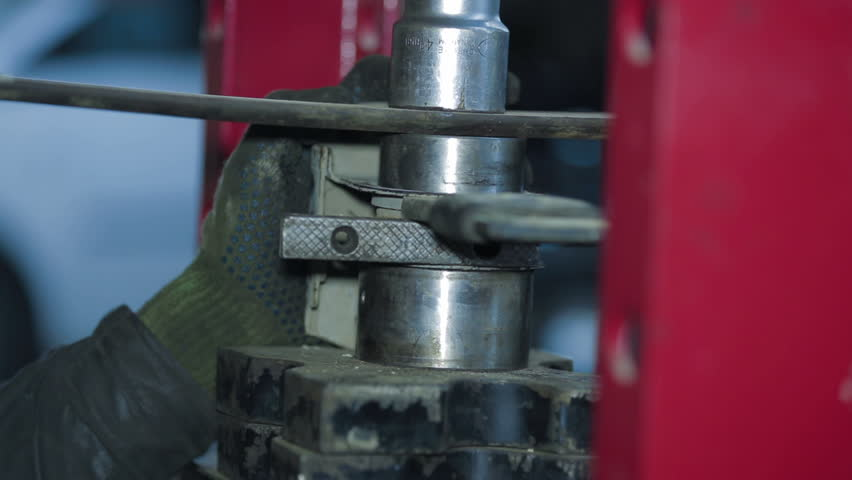 Close-up shot of mechaninc hands working with car parts.