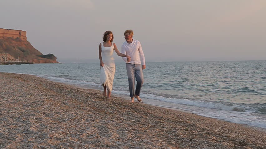 Young romantic couple walking on beach – slow motion