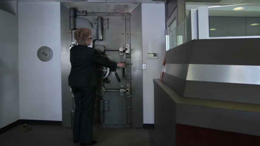 Woman opens a large bank vault door revealing the safe deposit boxes inside.
