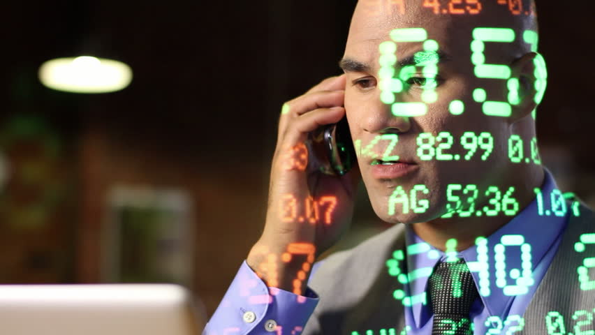 City guy making deals on the phone while ticker symbols of varying size are projected across him. Close up with dolly move past laptop screen edge. All ticker symbols are fictitious companies. | Shutterstock HD Video #3694505