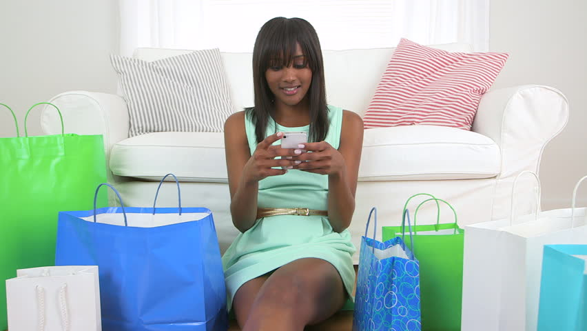 Black woman with shopping bags texting on mobile phone | Shutterstock HD Video #3698990