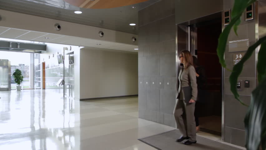 Business people get out of an elevator and walk through building atrium, towards