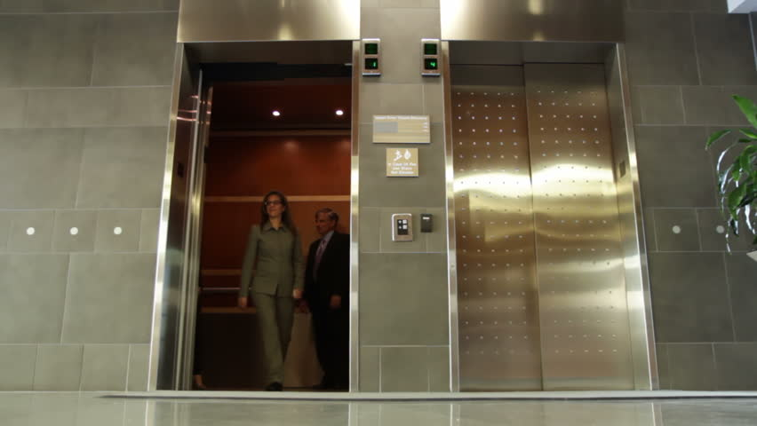 Business people get out of an elevator and leave frame. Wide view, recorded from