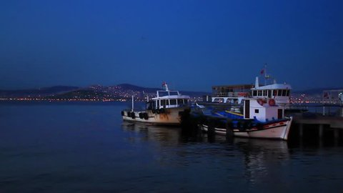 Fisher boats at berth in shore of Buyukada Island. Night scene with city lights on Islands
