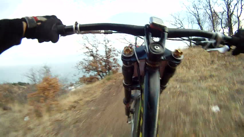 Two cyclists racing in a forest. Racing in a forest. pov.