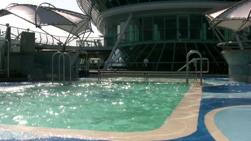 Outdoor swimming pool of large cruise ship during pitching. A bright sunny day.