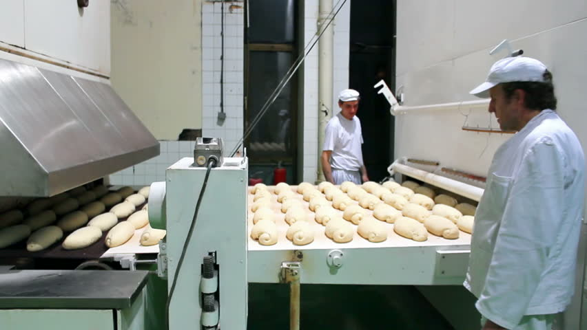 Bakery production line ; workers control the quality loaves of bread at the entrance the oven,video clip