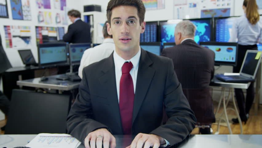 A young businessman is engaged in a video call with a client as seen from the pov of the computer screen. He is sitting at his desk in a busy office filled with computers.