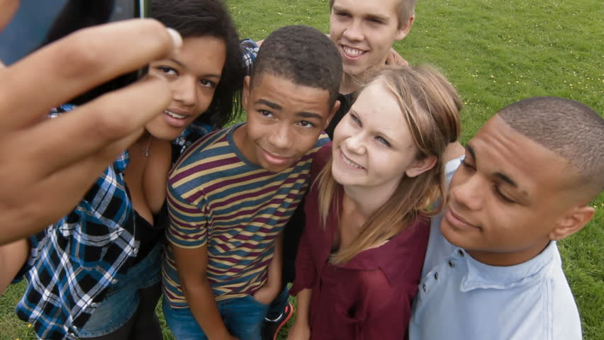 Taking a picture on a cell phone - Group of teenagers taking a photograph  on a