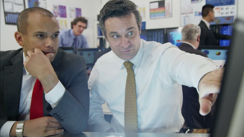 Two male financial traders are working in a busy office filled with computers. They are discussing market prices and profits, as the rest of their team are hard at work in the background.
