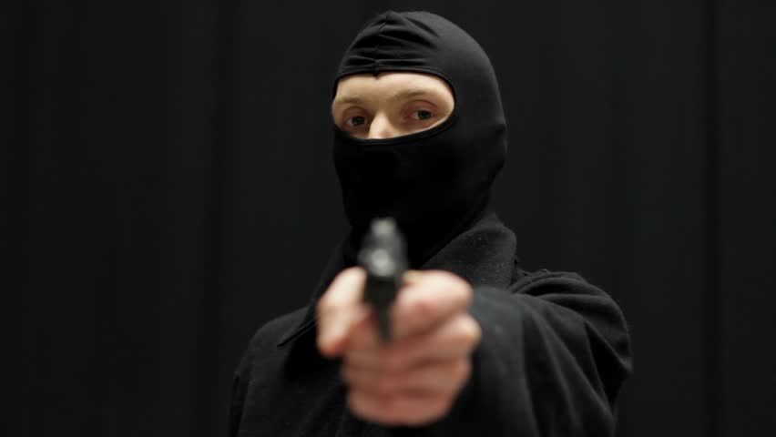 Male murderer in balaclava mask aiming at the viewer with a gun. Focus on the face.