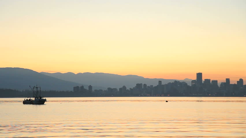 English Bay Dawn, Crab Boat, Vancouver. A commercial crab boat sets traps in English Bay at dawn with the Vancouver Skyline in the background. British Columbia, Canada.