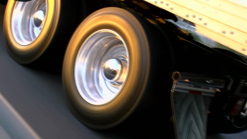 Truck tire wheels spin, close up, glow in late afternoon sun as rig rides smooth, open highway. 1080p #3817133