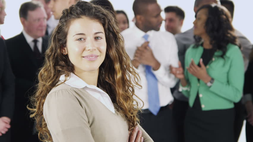 Portrait of a large group of happy and diverse business people who are standing together, isolated on white. One woman crosses her arms and smiles, with the rest of her team behind her. In slow motion