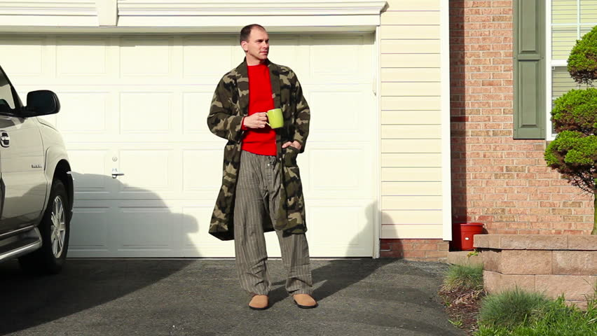A man in his robe awaits for his daily paper on the driveway.
