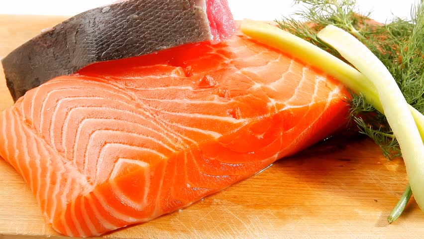 uncooked fresh salmon and red tuna fish pieces served over wooden board