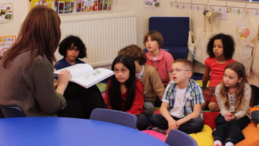 Storytime - a elementary / primary school teacher reading a story to a group of children