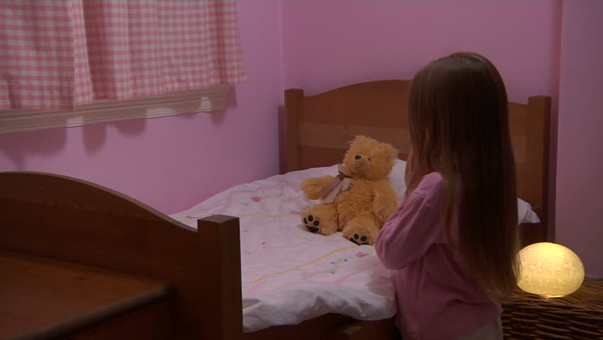 Little girl kneels to say her prayers before snuggling into bed