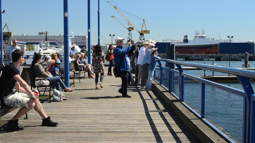 NORTH VANCOUVER, CANADA - MAY 5, 2013: Tourists and locals enjoy the sunshine on Lonsdale Quay. An early heatwave has broken records in southwest British Columbia this spring.