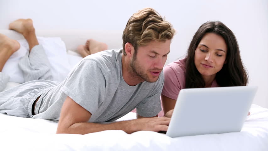 Couple using the laptop lying bed together at home