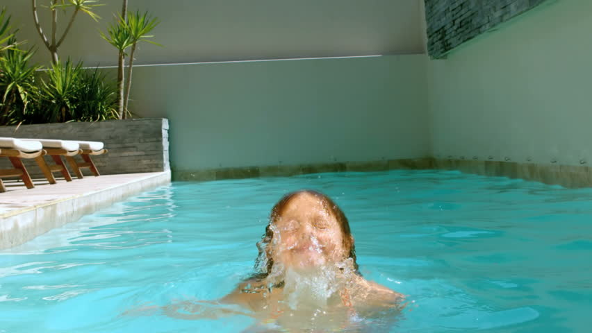 Young girl having fun in the swimming pool in slow motion at 250 frames per second