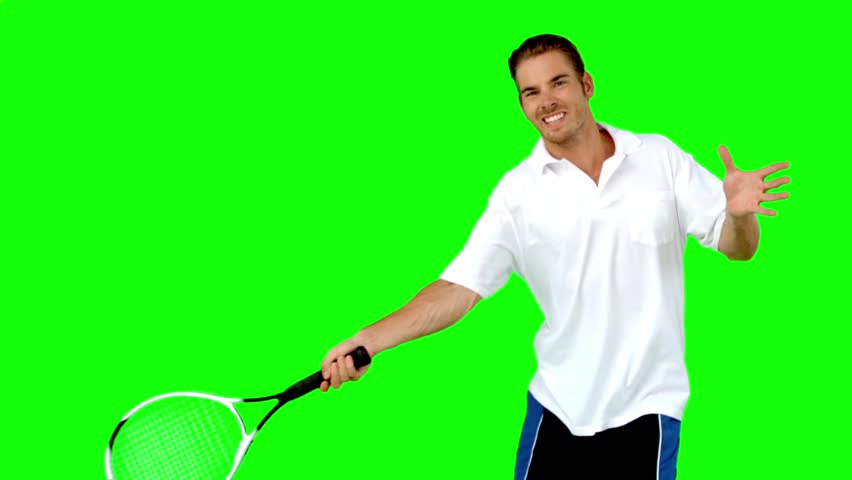 Young man playing tennis in slow motion on green screen #3871430