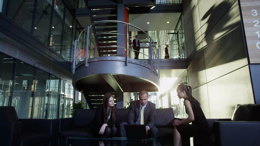 Diverse group of business people moving around and using communal spaces within a large modern office building. #3893462