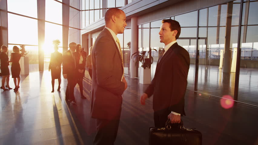Two young businessmen who are old acquaintances, meet and shake hands in a busy modern office building at sunset.  | Shutterstock HD Video #3894353