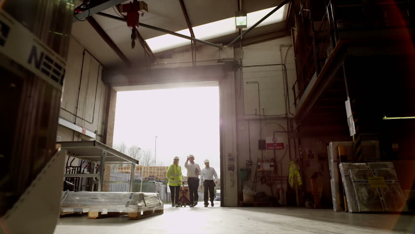A Team Of Workers In A Warehouse Receive A Delivery And Take It Into  Storage.