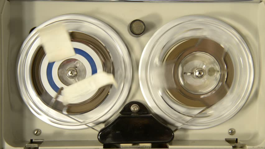 Aerial view of an old portable reel-to-reel mini tape-recorder while playing a tape on it
