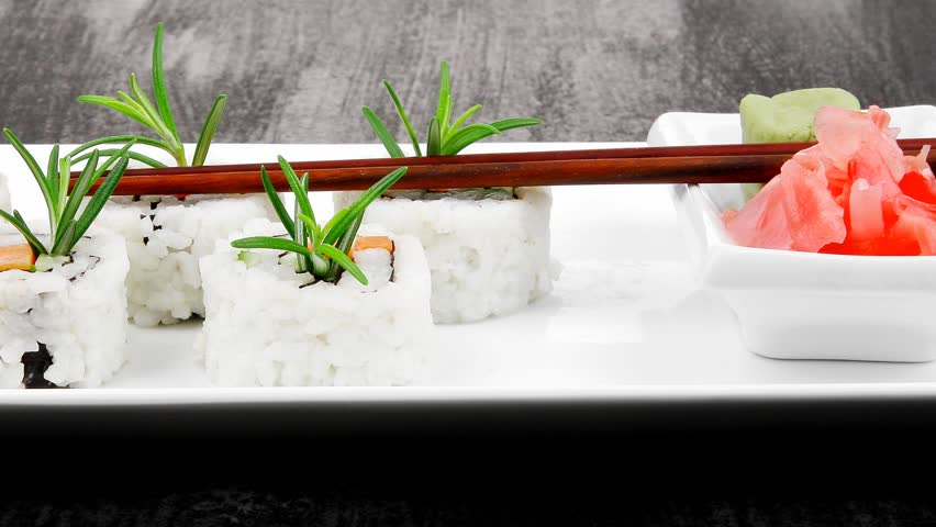 Japanese Cuisine - California Roll made of Salmon Cream Cheese and Avocado inside. Served with wasabi and ginger . on long white plate over black table 1920x1080 intro motion slow hidef hd