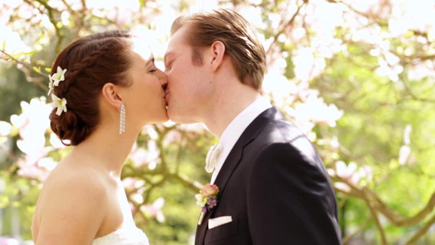 Bride and groom kissing under magnolia flowers