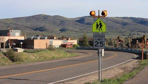 School bus passes a flashing 25 mph sign near a elementary school.