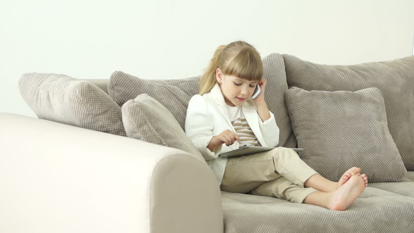Little girl sitting on the couch with a tablet and talking on the phone