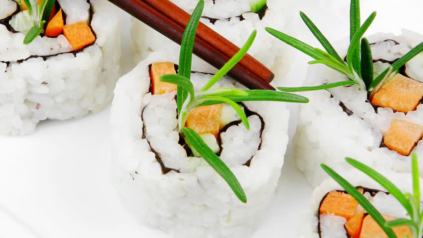 Maki Sushi - California Roll with Cucumber Cream Cheese and Salmon inside. Served with wasabi and ginger . on long white plate over black table 1920x1080 intro motion slow hidef hd