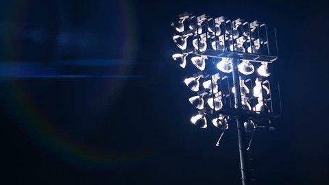 Stadium Lights turn on at sporting event.