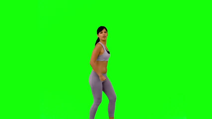 Athletic woman jumping and posing on green screen in slow motion #3996880