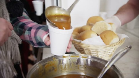 Close up of soup and bread being served to a waiting line of faceless homeless people.
