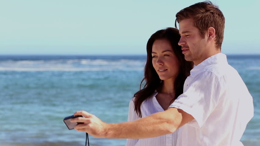 Couple taking a self portrait together on the beach