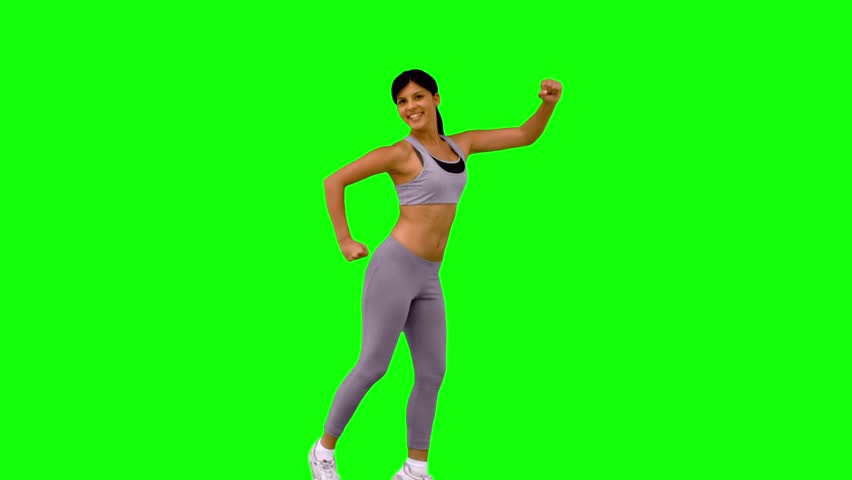 Athletic woman leaping and posing on green screen in slow motion #4049380