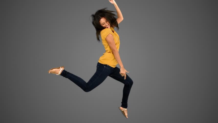 Woman jumping on grey background in slow motion