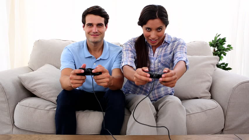 Couple playing at video game in their living-room