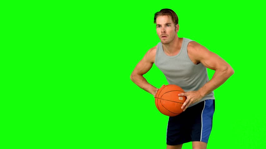 Basketball player passing the ball in slow motion on green screen